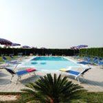 overzicht zwembad Tenuta Regina met ligbedden en parasols